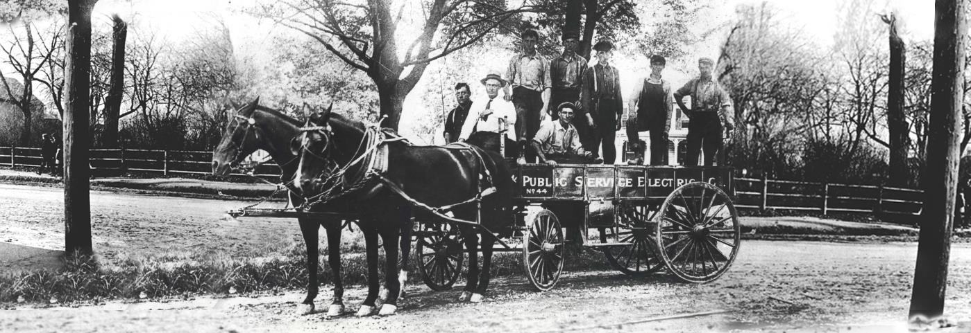 Public Service Employee pose with a horse drawn wagon