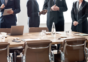 Executives talking with each other on the side of a board room table