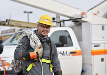 PSE&G Lineman smiling with rope around shoulder